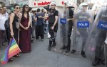 epa04822889 Activists face Turkish riot police blocking a road during a rally on the occasion of the 13th annual Gay Pride Parade in Istanbul, Turkey, 28 June 2015. Numerous LGBT (Lesbian, Gay, Bisexual, Transexual) activists and supporters were marching through downtown Istanbul to support rights for sexual minorities. Leaders of the 13th annual Istanbul LGBTI Pride Parade said police used force on the tens of thousands of people who had arrived at the city's central Taksim Square waving rainbow flags and holding placards.  EPA/TOLGA BOZOGLU