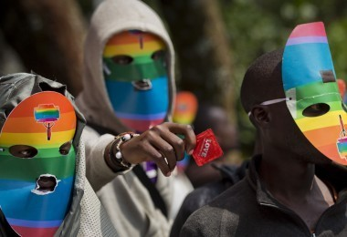 "FILE - In this Monday, Feb. 10, 2014 file photo, Kenyan gays and lesbians and others supporting their cause wear masks to preserve their anonymity and one holds out a condom, as they stage a rare protest, against Uganda's increasingly tough stance against homosexuality and in solidarity with their counterparts there, outside the Uganda High Commission in Nairobi, Kenya. Ugandan President Yoweri Museveni met in his office with a team of U.S.-based rights activists concerned about legislation that would impose life sentences for some homosexual acts and made clear he had no plans to sign the bill, according to Santiago Canton of the Robert F. Kennedy Center for Justice and Human Rights who attended the Jan. 18, 2014 meeting, but one month later Museveni appears to have changed his mind, saying through a spokesman in February 2014 that he would sign the bill ""to protect Ugandans from social deviants."" (AP Photo/Ben Curtis, File)"