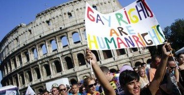 A woman holds her banner in front of the Colosseum during the annual gay pride parade in downtown Rome June 15, 2013. REUTERS/Max Rossi (ITALY - Tags: SOCIETY)